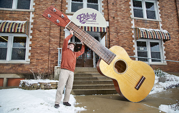Holding up the largest ukulele