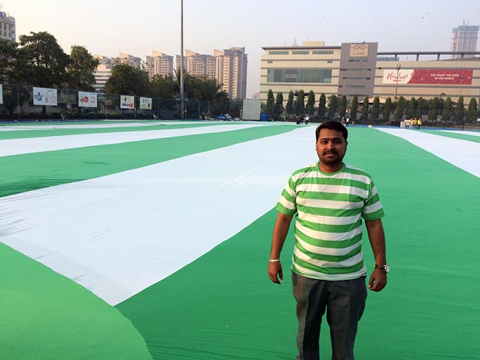 A man stands on the largest t-shirt, wearing a normal-sized version