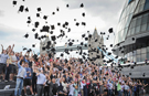 International students break record largest mortar board toss