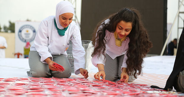 Students creating the largest cookie mosaic in Jordan