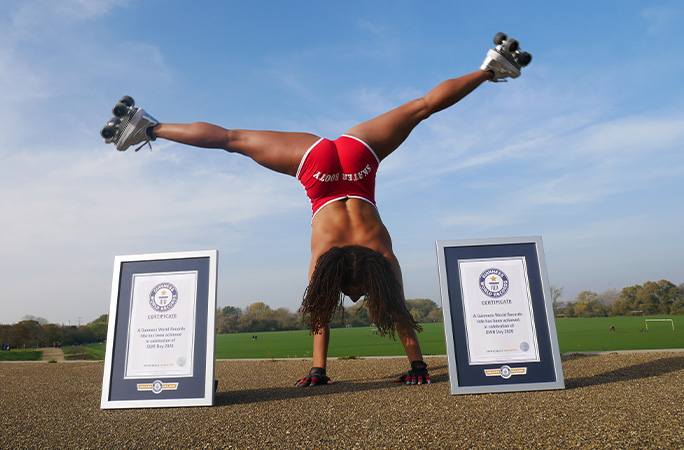 Tinuke Orbit doing a handstand split with her certificates