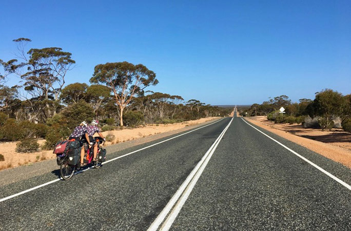 cat and raz cycling down the longest straight road in Australia